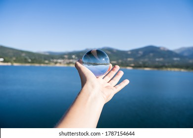 Hand of a person holding a crystal ball reflecting the landscape of a lake with mountains in a water reservoir in Navacerrada in the Sierra in Madrid