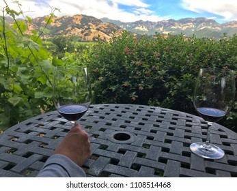 Hand of a person holding a glass of red wine on a table gazing out over Napa Valley vineyards. Green vineyards in mid-ground, hills and blue sky in background.