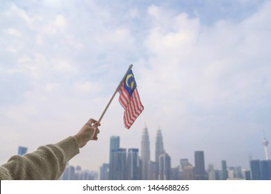 Hand Of Person Holding Malaysia Flag Against KL skyline. Celebrate Independence Day & Merdeka day.