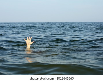 hand of the person seeks help while he is drowning in the middle of the sea