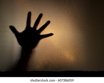 Hand of a person with stretched fingers behind an opaque and obscure glass