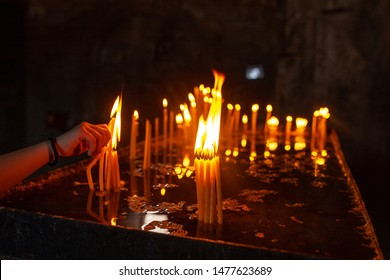 hand of a person who believes in Christ holds a wax candle burning with a warm flame in front of the altar during a prayer to God, a traditional religious ritual in an ancient temple, ask God for help