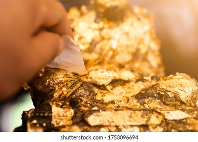 The hand of the person who is gilding the Buddha statue  Close-up
