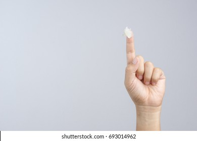 Hand with petroleum jelly on index finger on white background