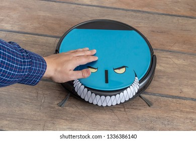 Hand petting a robot vacuum cleaner. Evil robots and takeover concept.