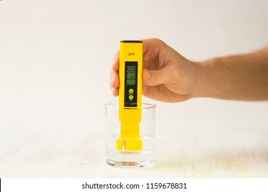 A hand with a PH measuring instrument. Bad indicators of drinking water. Rigid water. Tap drinking water quality control showing a high level of TDS Total dissolved solids