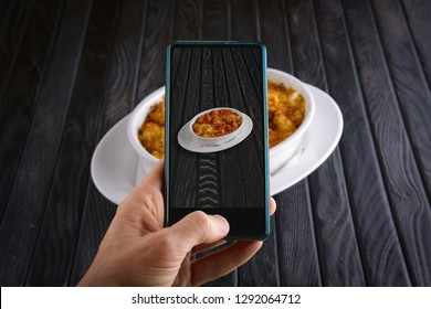 Hand with phone. Blogger making photo of food. Pasta baked with shrimps and cheese