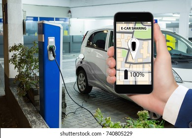 Hand with phone on a background of electric cars charging point. E-car sharing concept