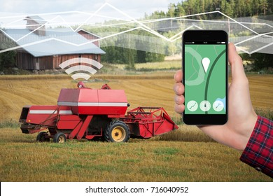 Hand with phone. On the screen control interface of the self driving combine harvester. Internet of things in agriculture.