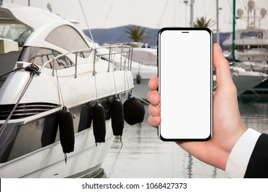 Hand and phone with white screen. On a background luxury yacht.