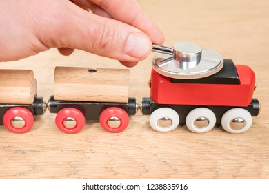 hand with a phonendoscope on the roof of the locomotive of a toy train standing on a wooden table