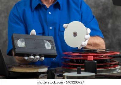 hand photographer holding a VHS tape and DVD disc for conversion