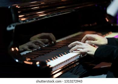 Hand of pianist in jazz lighting