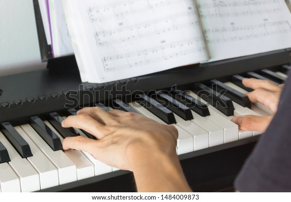 Hand of Piano Player on White Keys and Black Keys of Electric Piano with Piano Staff or Sheet Music