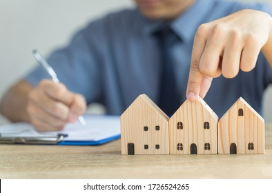 Hand pick House Wooden model in real estate , seller or buyer , loan concept with blur loan employee or realtor he's checking details about the sale of the house ,home Mortgage or home lone