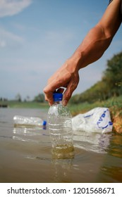 hand pick up plastic water bottle from river. save environment and beat plastic pollution.