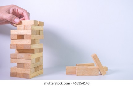 hand pick up wooden  block to make structure isolated on white background,planning in business model