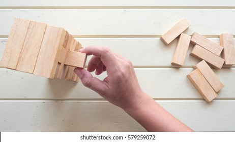 hand pick up wooden block to make structure on wood background,planning in business model