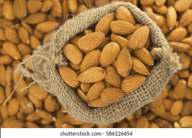 Hand picked high quality bunch of Almonds in burlap sack over large pile of almonds background