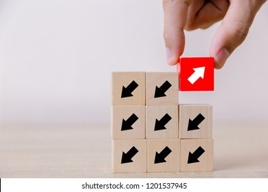 Hand picked red wooden blocks with white arrows facing opposite to the black arrows. With different concepts to other people. Going for success.