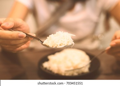 Hand picked spoon to eating white rice in the dish.Vintage style.