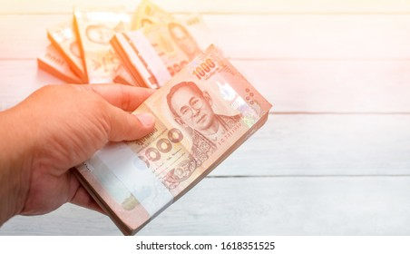 Hand picked a wad of Thai banknotes fromd many wad of Thai banknotes on white wooden background. focus on hand picked a wad of Thai banknotes. Kind of thousand Thai baht. Money concept.