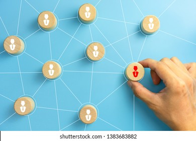 Hand picked a wooden cubes with person icon on blue background, Organisation structure, social network, leadership, team building, recruitment business, management and human resources concepts.