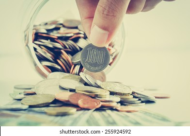 Hand picking up 100 Japanese yen (JPY) coin out of multi currency pile of coins - vintage style color effect
