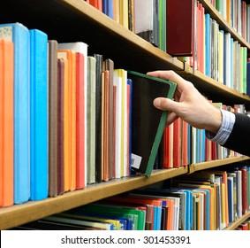 Hand picking book in library bookshelf