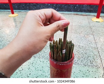 A hand is picking a Chi-Chi Stick, Fortune stick or Seam Si at Chinese shrine in Thailand. It's made from bamboo. By have to  shake it to get a number and then see the fortune paper same as number.