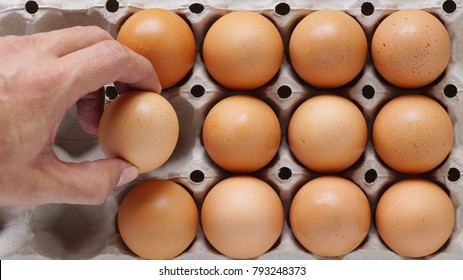 Hand picking eggs which lay on the paper tray close up.