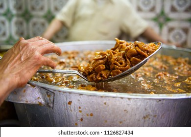 Hand picking up fried sweed in a big pan, Morocco