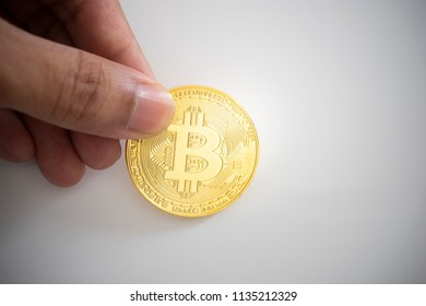 Hand picking golden Bitcoin Cryptocurrency