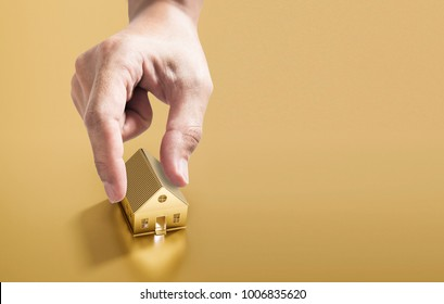 Hand picking golden house, real estate investment and buying house and property concept