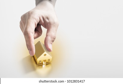 Hand picking golden house, real estate investment and buying house concept
