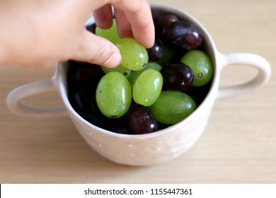 Hand picking a grape from a ceramic bowl. Selective focus.