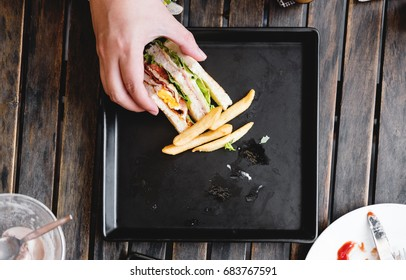 Hand picking last piece of sandwich, on square black dish, on wooden table