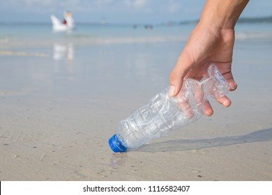 Hand picking up plastic bottle cleaning on the beach.