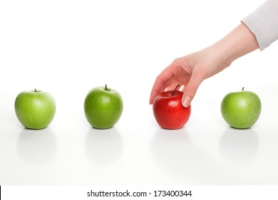 Hand picking red apple among green apples