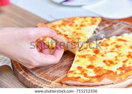 Hand Picking Up A Slice Of Cheese Pizza