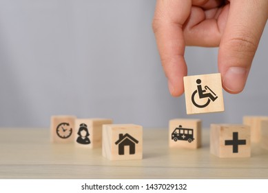 hand picking up wooden block with icons related to disability, medical, rehabilitation service, nursing care. can use for medical and rehabilitation concept article, banner, brochure in handicap.