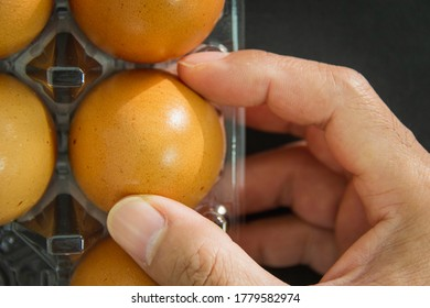 hand picks up the eggs from the plastic package that are placed on the wooden table