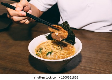 Hand pinching Chashu Pork in Hakata style Shio Chashumen (Salt soup) with chopsticks including noodle, sprout, seaweed and scallion.