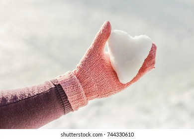 Hand in pink glove holding snow heart. Winter time