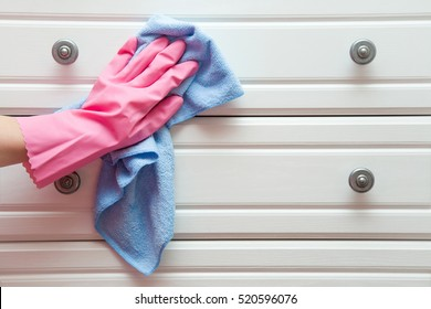 Hand in pink protective glove cleaning wooden furniture with rag. Early spring cleaning or regular clean up. Maid cleans house.