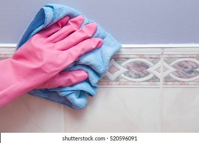 Hand in pink protective glove cleaning tiles with rag in the bathroom. Early spring cleaning or regular clean up. Maid cleans house