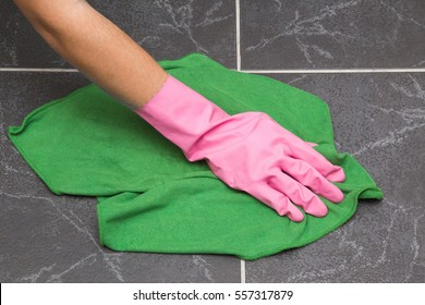 Hand in pink protective glove cleaning tiles with rag in the bathroom. Early spring cleaning or regular clean up. Maid cleans house.