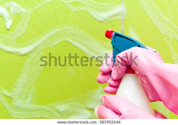 Hand in pink protective glove holding spray bottle to clean tiles. Early spring cleaning or regular clean up. Maid cleans house.