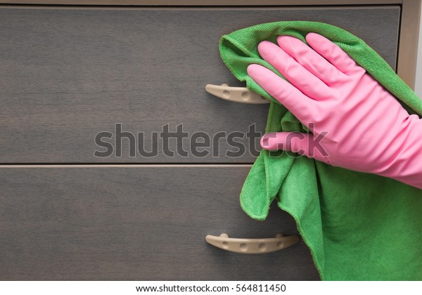 Hand in pink protective glove wiping wooden furniture with rag. Early spring cleaning or regular clean up. Maid cleans house.