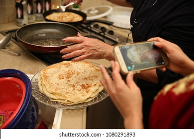 Hand places the Jewish ethnic food called 'mufleta' on a platter while someone takes a cell phone picture. This food is traditionally made at the end of the Passover holiday